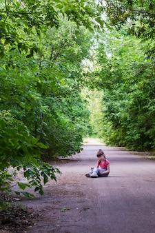 Uma menina de cabelos escuros de nove anos sentada sozinha em uma estrada cinza no meio de uma floresta com árvores verdes