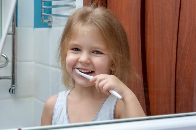 Uma menina de cabelos loiros, escovando os dentes.