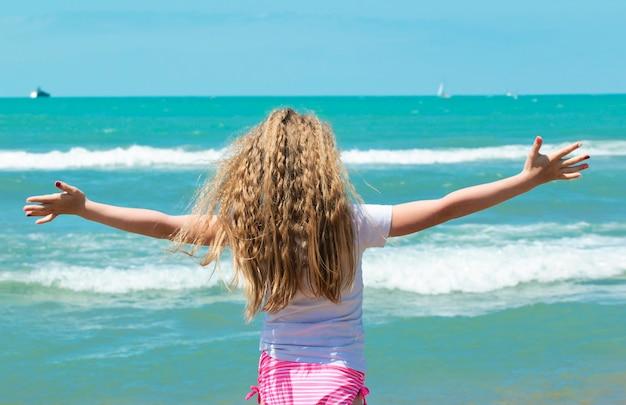 Uma menina de cabelos loiros gosta de bom tempo e do mar no verão nas férias. olá, mar!