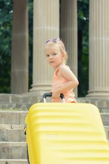 Uma menina de cabelos loiros levanta uma grande mala amarela nos degraus.