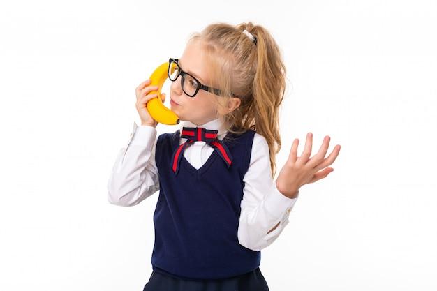 Uma menina de cabelos loiros, recheados de rabo de cavalo, grandes olhos azuis e um rosto bonito em óculos quadrados pretos fala sobre uma banana