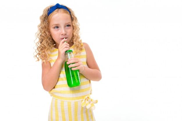 Uma menina de cabelos vermelhos em um terno de verão listrado branco e amarelo, com um curativo azul na cabeça bebe suco de laranja em uma garrafa de vidro de cachimbo.