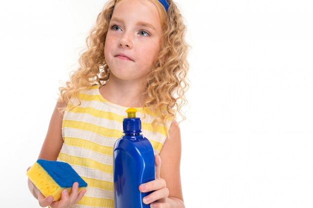 Uma menina de cabelos vermelhos em um terno de verão listrado branco e amarelo, com um curativo azul na cabeça com uma esponja e detergente