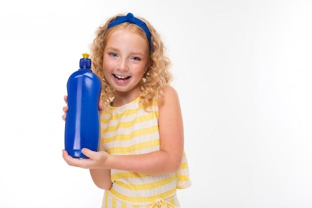 Uma menina de cabelos vermelhos em um terno de verão listrado branco e amarelo, com um curativo azul na cabeça com uma esponja e detergente.