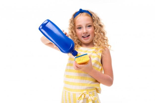 Uma menina de cabelos vermelhos em um terno de verão listrado branco e amarelo, com um curativo azul na cabeça começa a lavar a louça.