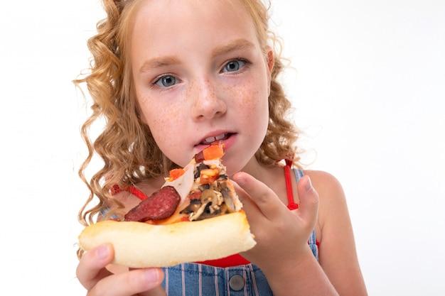 Uma menina de cabelos vermelhos em uma camisa vermelha e macacão azul e branco em uma faixa come uma pizza grande.