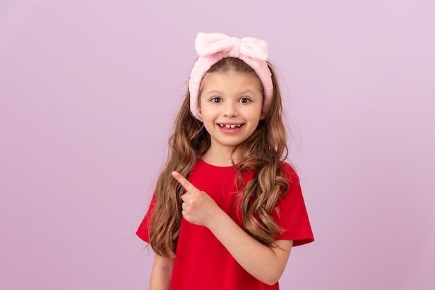 Uma menina de camiseta vermelha aponta o dedo para o anúncio.