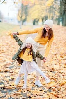 Uma menina de cinco anos, abrindo a boca com admiração e alegria, brinca com a mãe no parque de outono. mãe e filha se divertem ao ar livre no outono