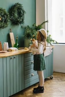 Uma menina de cinco anos, com roupas elegantes de flores brancas e verdes, está segurando um saco de papel com uma baguete, em pé perto da cozinha, decorada para o natal