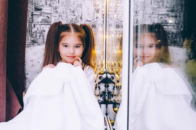 Uma menina de cinco anos está sentada no peitoril da janela, envolta em uma manta branca, sorrindo. reflexo na janela de uma menina.