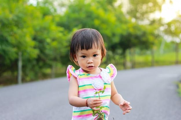 Uma menina de criança em pé e segurando uma grama floresce nas mãos no parque natural.