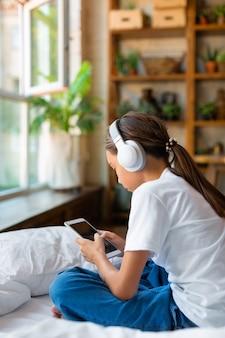 Uma menina de dez anos está sentada na cama com um telefone celular, ela ouve música com fones de ouvido