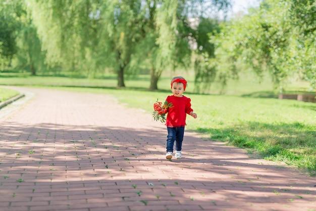 Uma menina de dois anos corre pelo parque com um buquê e uma expressão séria no rosto