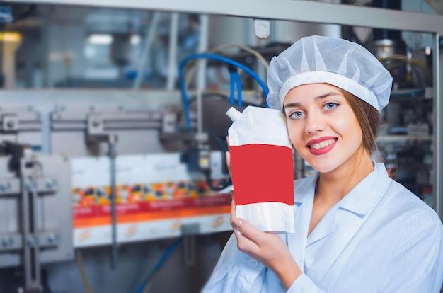 Uma menina de macacão branco e um cocar na linha de produção de alimentos