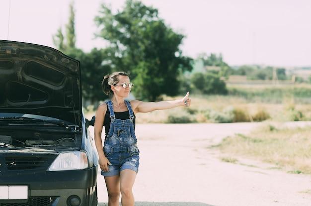 Uma menina de macacão jeans ao lado de um carro com o capô aberto levanta o dedo tentando parar o carro