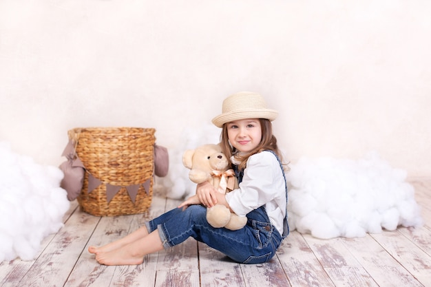 Uma menina de macacão senta-se no chão com um ursinho de pelúcia na parede de um balão e nuvens. menina está sonhando. menina brinca no quarto infantil com um brinquedo. criança pequena e brinquedo de pelúcia