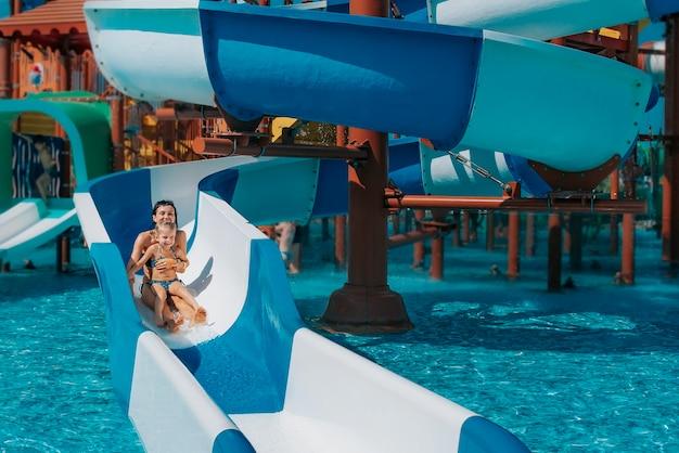 Uma menina de maiô desce os escorregadores azuis até a piscina, mãe e filha, brincando e nadando na piscina ao ar livre