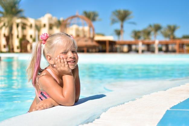 Uma menina de maiô senta-se na água azul de uma piscina em um hotel com palmeiras