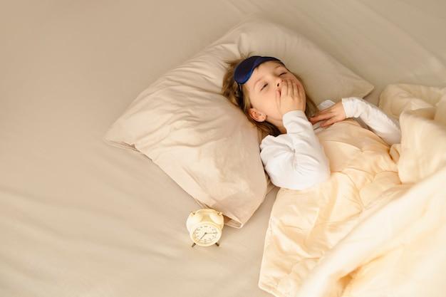 Uma menina de manhã está deitada na cama e boceja, cobrindo a boca com a mão