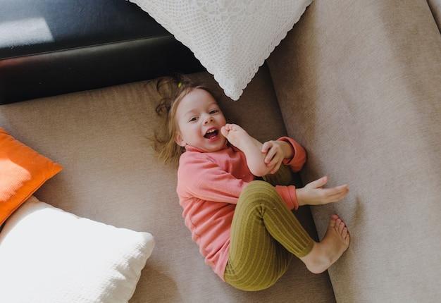 Uma menina de moletom rosa está deitada no sofá entre os travesseiros, com as pernas para cima. jogos caseiros.