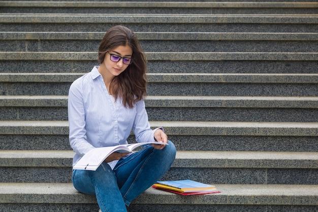 Uma menina de óculos com um livro fica nos degraus