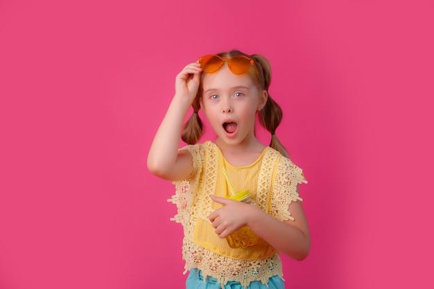 Uma menina de óculos escuros com um coquetel rosa