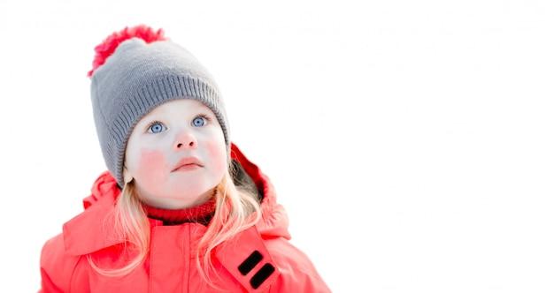 Uma menina de olhos azuis em um chapéu de malha e uma jaqueta de inverno rosa olha para cima. close up, isolado no branco