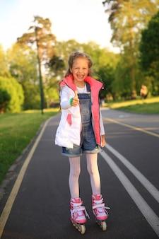 Uma menina de patins faz um gesto com o polegar para cima no parque