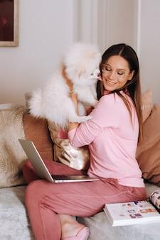Uma menina de pijama em casa está trabalhando em um laptop com seu cachorro spitzer, o cachorro e seu dono estão descansando no sofá e assistindo o laptop. tarefas domésticas.