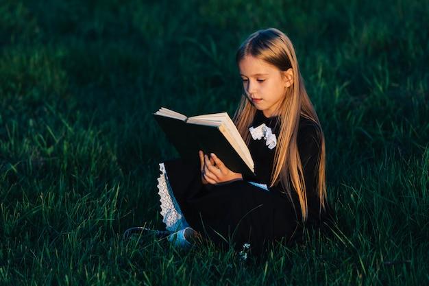 Uma menina de preto senta-se na grama e segura um livro verde à luz do sol poente. uma criança lê ao ar livre na natureza.
