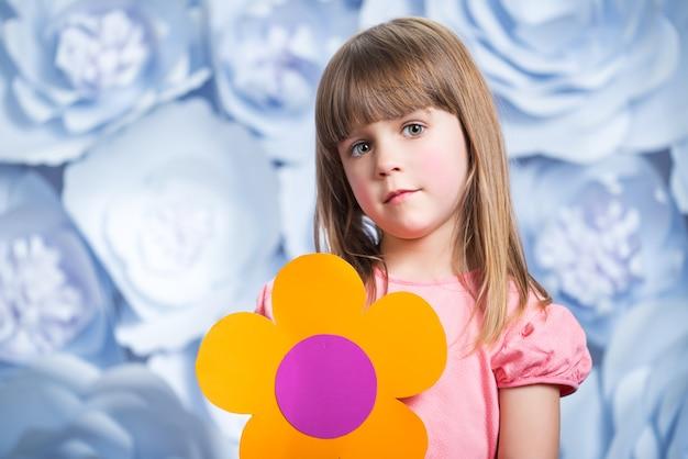 Uma menina de rosto calmo segura nas mãos uma flor decorativa de papel amarelo