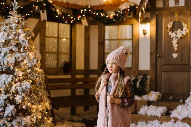 Uma menina de seis anos em um chapéu de malha rosa com pompom e um colete de pele rosa fica perto de uma árvore de natal e uma casa decorada com um feriado e ano novo