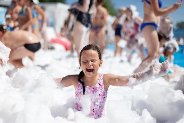 Uma menina de seis anos em um maiô rosa está chorando alto em uma festa de espuma que ela se perdeu em uma viagem e está ...