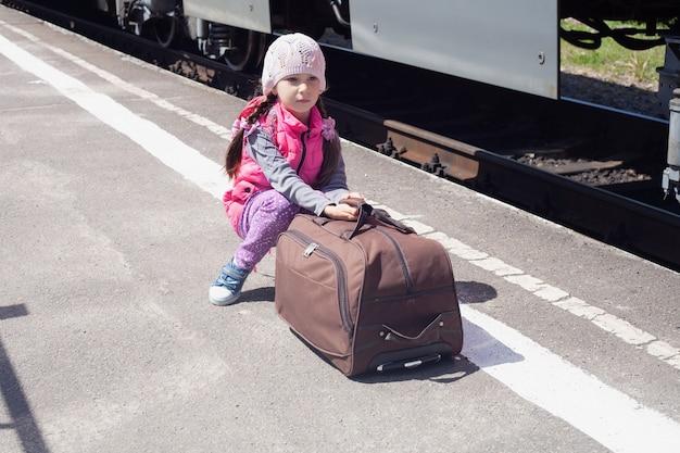 Uma menina de seis anos está sentada na plataforma da estação com uma mala.