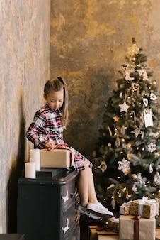 Uma menina de seis anos senta-se em uma cômoda com um vestido branco vermelho e azul contra uma árvore de natal e abre o presente de ano novo