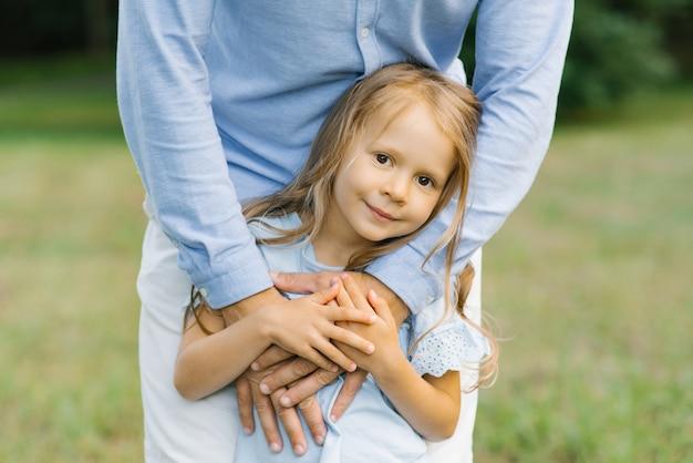 Uma menina de seis ou cinco anos de vestido azul segura as mãos do pai e sorri docemente