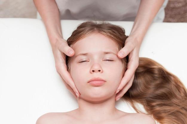 Uma menina de sete anos em uma consulta com um osteopata. osteopatia pediátrica. dores de cabeça em crianças em idade escolar. correção do crânio, coluna vertebral.