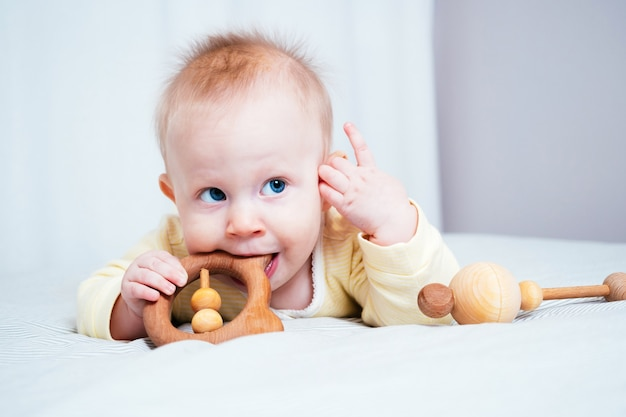 Uma menina de sete meses com olhos azuis está deitada de bruços em uma sala iluminada e mordisca um brinquedo de madeira, olhando para cima. os dentes da criança estão começando a aparecer, as gengivas coçam. conceito de saúde infantil.
