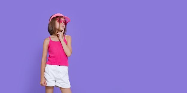 Uma menina de short branco, camiseta rosa, óculos rosa da moda e viseira de verão Foto Premium