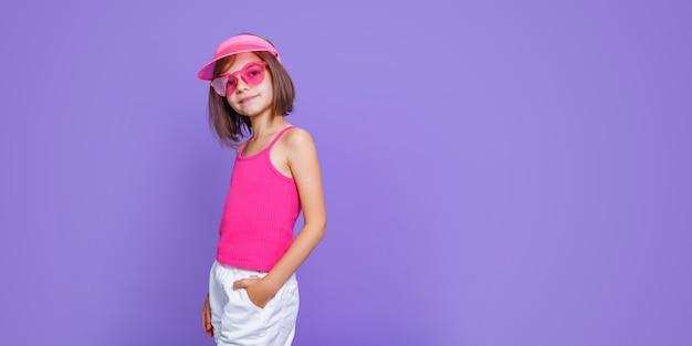 Uma menina de short branco, camiseta rosa, óculos rosa da moda e viseira de verão