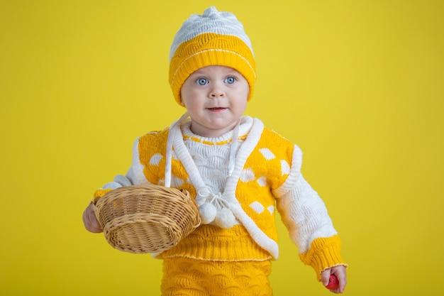 Uma menina de um ano de idade com roupas amarelas e ovos de páscoa em um fundo amarelo expressa emoções