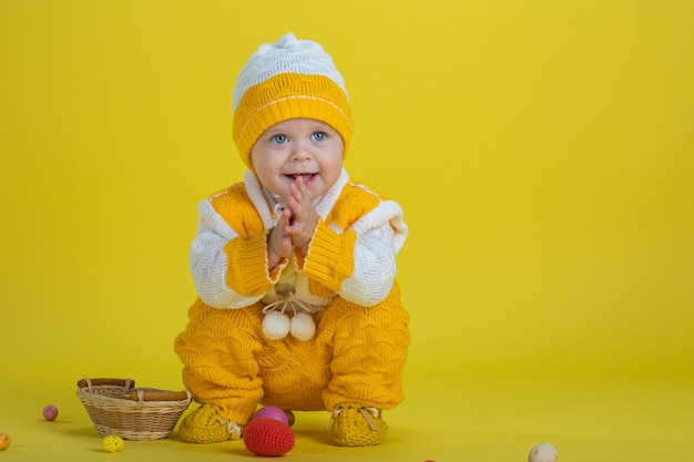 Uma menina de um ano de idade com roupas amarelas e ovos de páscoa sentada em um fundo amarelo expressa emoções