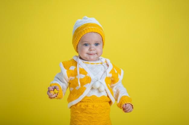 Uma menina de um ano de idade com roupas amarelas em um fundo amarelo expressa emoções