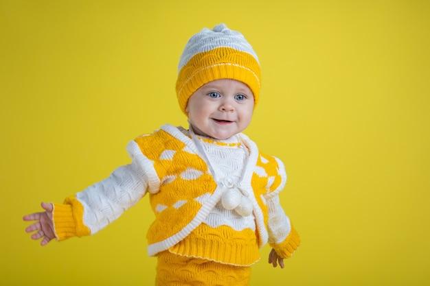 Uma menina de um ano de idade com roupas amarelas ficará surpresa, acenando com as mãos em um fundo amarelo e expressando emoções