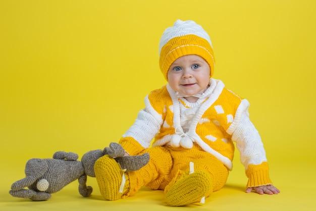 Uma menina de um ano de idade com roupas amarelas sentada sobre um fundo amarelo expressa emoções