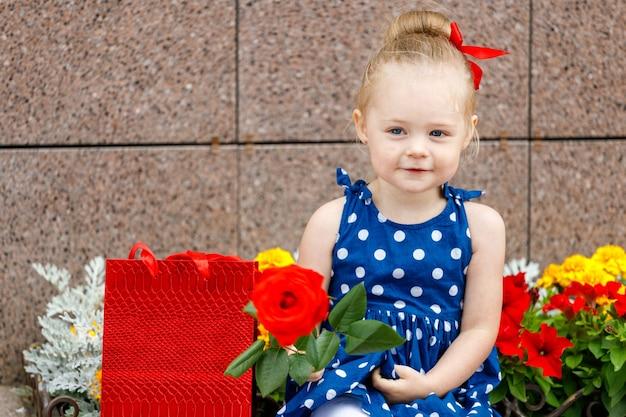 Uma menina de vestido azul e laço vermelho sentada com sacolas coloridas na rua ao lado de flores