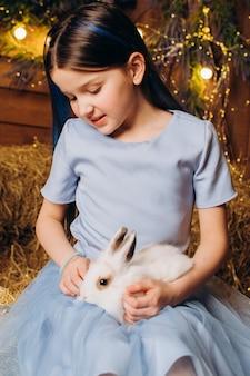 Uma menina de vestido azul sentada em uma fazenda com um coelho