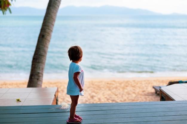 Uma menina de vestido branco olha para o mar em pé no chão de madeira do lado de fora