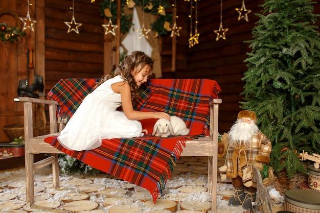 Uma menina de vestido branco, sentado no banco com coelho branco.