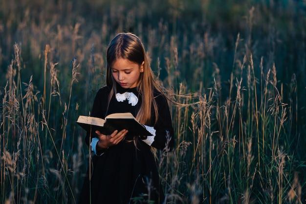 Uma menina de vestido preto fica na grama alta e lê um livro verde à luz do sol poente.